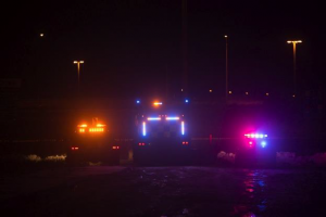Tow truck, snow plow, and police car at night