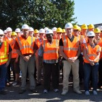 Group of people at a site tour wearing hard hats and reflective vests