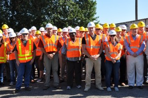 Group of people at a facility tour wearing hard hats and reflective vests